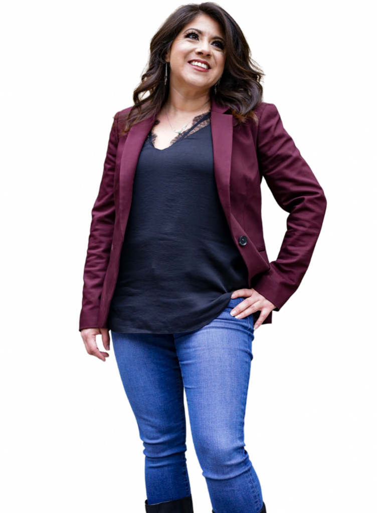 Wendie V standing in a burgundy blazer black shirt and jeans with left hand on her hip