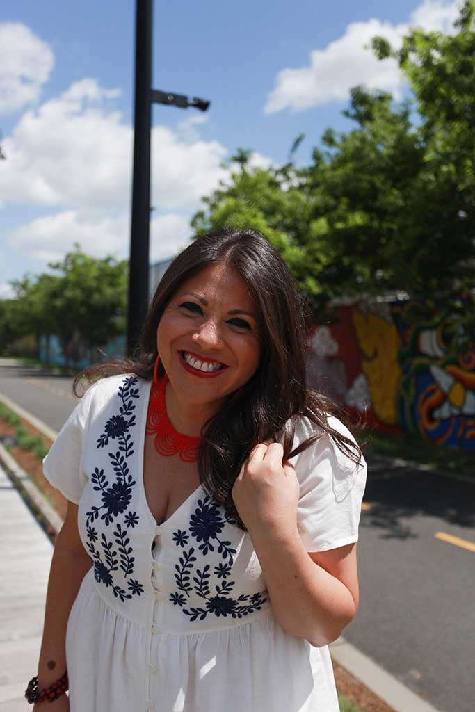 Wendie Veloz in a white dress with blue flowers smiling with long curled brown hair and red necklace in front of a blue sky with clouds.
